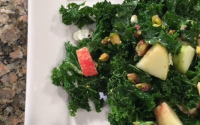 Kale apple salad with feta cheese and pistachios in orange dressing